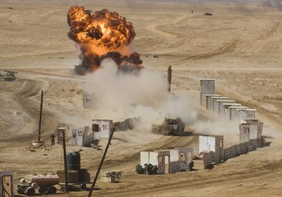 Israeli soldiers take cover behind a mock building, as a tank fires during a large military exercise at the Shizafon Armored Corps Training Base in the Arava desert, north of the city of Eilat, southern Israel, Tuesday, Oct. 12, 2010. (AP Photos/Dan Balilty)