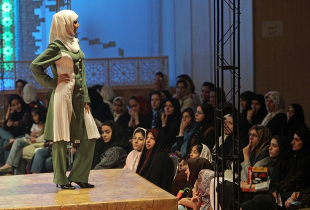 """Iranian women watch a model on the catwalk displaying traditional and Islamic clothes from different Islamic countries during the """"Women From My Homeland"""" fashion festival in Tehran, 08 July 2007. The 10-day international festival including Islamic fashion shows and exhibitions started last week in Tehran. AFP PHOTO/BEHROUZ MEHRI / AFP PHOTO / BEHROUZ MEHRI"""