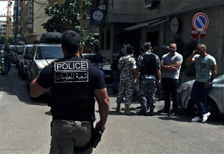 """Lebanese police intelligence gather outside a hotel after security forces raided there in Beirut's Hamra district, Lebanon, Friday, June 20, 2014. Security forces raided the hotel over suspected """"terrorist cells"""" inside it, a police official said. In eastern Lebanon, a suicide bomber detonated his vehicle Friday near a police checkpoint, killing a few people amid heightened concerns of renewed violence, the country's state-run news agency and security officials said. (AP Photo/Bilal Hussein)"""