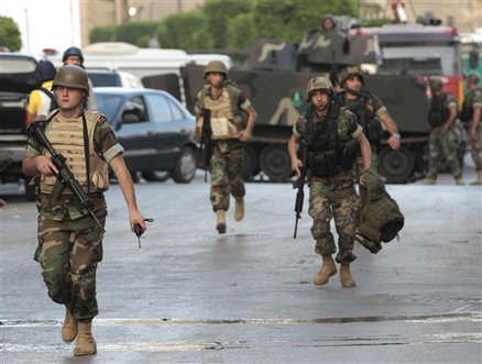 Lebanese army soldiers run to support their comrades clashing with a Syrian gunman who had engaged in an hours-long shootout with security forces, in Beirut, Lebanon, Thursday, May 24, 2012. Security officials say troops stormed an apartment in west Beirut, killing a Syrian gunman who had engaged in an hours-long shootout with the security forces. The officials say the gunman first shot at the troops on the street in Caracas neighborhood, then fled to his apartment, which the soldiers stormed early Thursday. The body of another man was found in the apartment but it's unclear how he died. Five soldiers and policemen were also wounded in the gunbattle which caused panic among residents in the area. (AP Photo/Hussein Malla)
